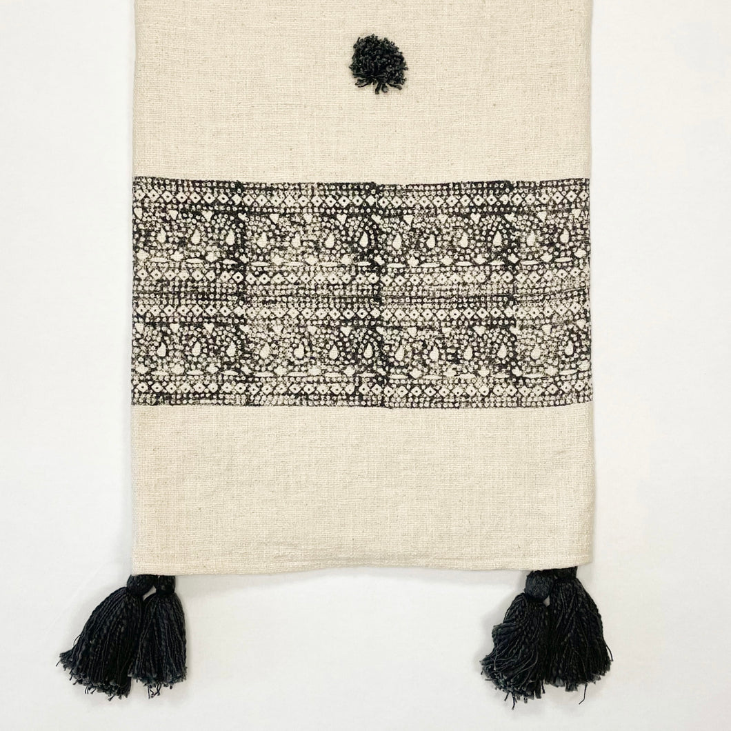 The Ira Throw is the perfect way to layer on some boho sophistication. The cream slub cotton throw is block printed with an intricate black border and finished with handmade black poms and tassels. Artisan made, limited edition. Measures 49
