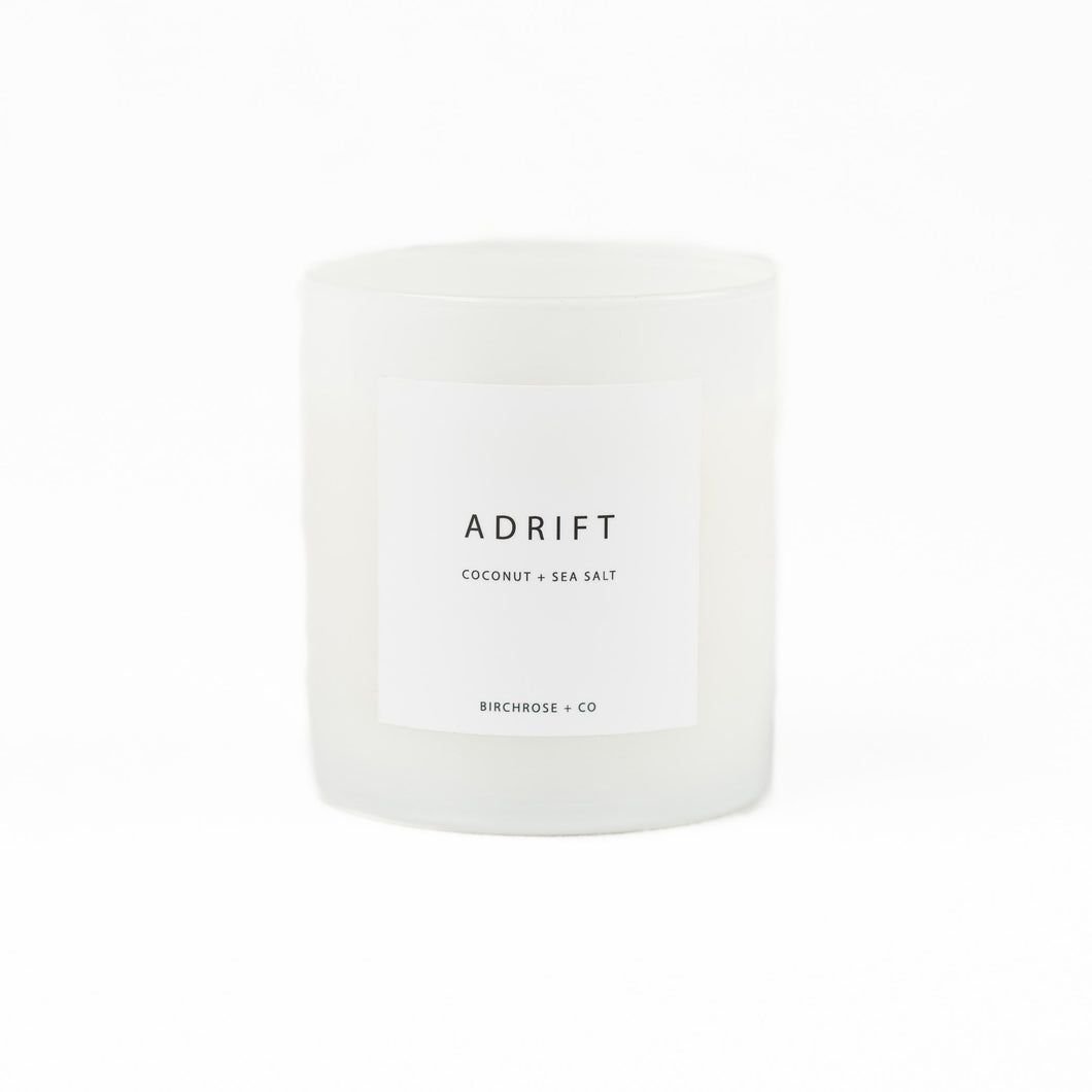 ADRIFT candle in white high gloss glass vessel. Coconut and Sea Salt scent.