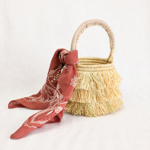 Artisan-made basket bag with raffia fringe