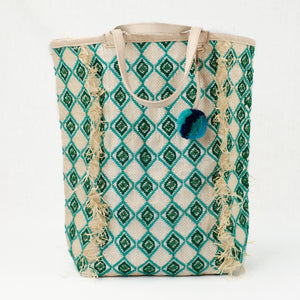 Jade and green beach tote embroidered with a diamond pattern. Natural leather handle and charm with green and blue pom pom.