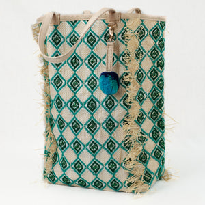 Beach tote made from recycled grain bag and raffia with natural leather handles. Green and jade diamond pattern is embroidered all over bag with raffia fringe trim.