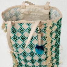 Load image into Gallery viewer, Close up view of leather handles, interior zip pocket and green and blue pom-pom charm.