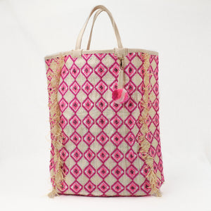Pink and Fuchsia embroidered beach bag made from a recycled grain bag and raffia. All-over diamond pattern embroidery with a leather and bright pink pom-pom charm.