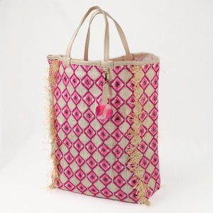 Pink embroidered beach bag made from recycled grain bag by EnShallah. Bag has all-over pink diamond pattern, leather handles, raffia fringe trim and pink pom-pom charm.