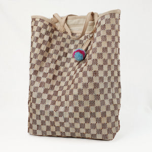 Brown and natural checkered beach tote made from a recycled grain bag. Straps and trim made of natural lamb leather.