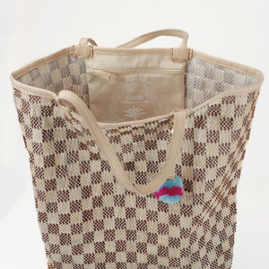 Interior view of brown and natural checkered beach tote with interior zip pocket. Natural lamb leather handles and trim with pale blue and hot pink pom-pom charm.