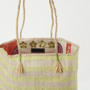 Interior view of recycled grain bag and zip pocket. Exterior is natural and yellow stripes with raffia handle.
