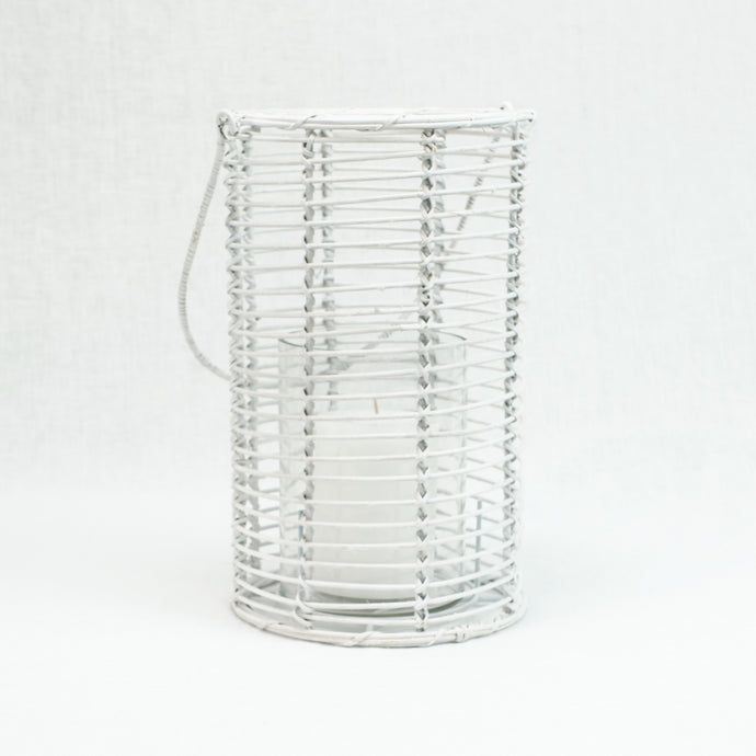 Lantern made of white washed cane with glass candle holder inside.