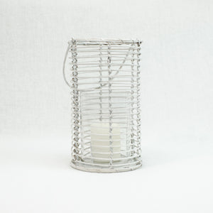 Lantern made of white washed cane with glass candle holder. Swivel handle.