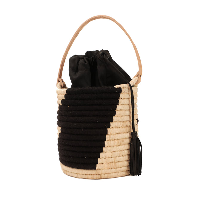 Black and natural woven raffia basket tote with natural leather handle.