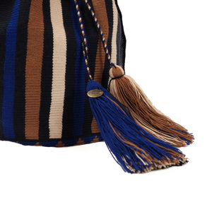 Close up image of handmade tassels finishing off the drawstring closure on the bucket bag.