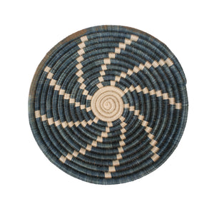 Small basket woven in a bowl shape. Dyed natural and indigo grasses create a spiral sunburst motif.