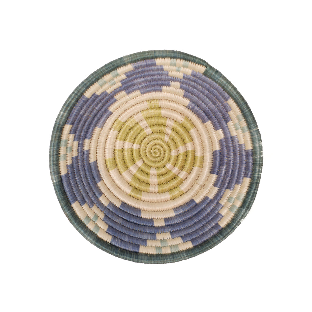 Small bowl shaped basket in shades of soft blue, purple, lime and natural corded grasses. Hand woven by artisans in Africa.