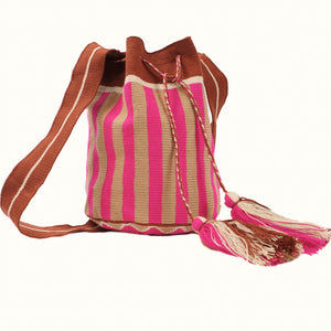Soft woven bucket bag in fuchsia and tan stripes with a sepia and white strap. Drawstring closure is finished with fuchsia, tan & white tassels.