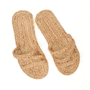 Strappy slip on beach sandal made of woven raffia with a foam rubber sole.
