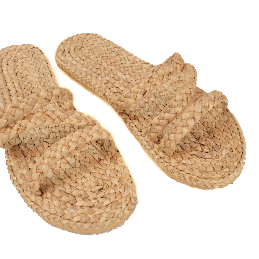 Slip on sandal made of raffia with rubber foam sole. Three straps go across the top of foot.