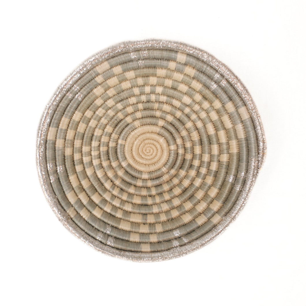 Small basket woven in a bowl shape using natural and soft grey dyed grasses to create a floral star pattern. Handmade by artisans in Africa.