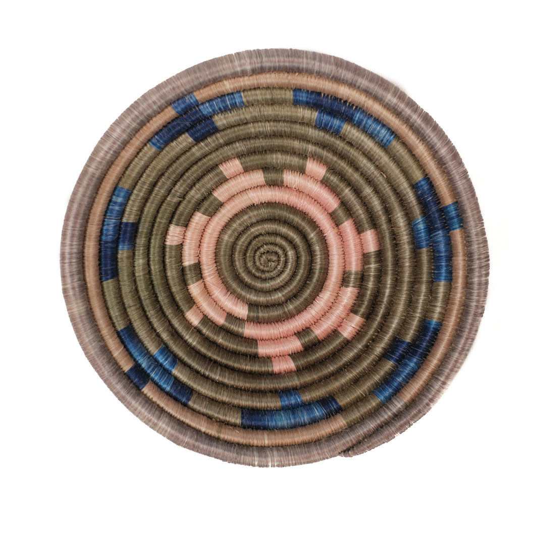 Woven corded basket in a small bowl shape. Woven in taupe, soft pink and indigo colors making a graphic pattern.