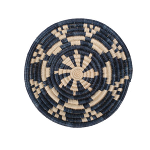 Small basket woven into a bowl shape. A graphic star-like motif is created using natural and indigo dyed grasses.