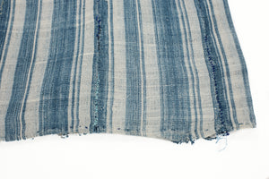 Indigo and cream striped vintage cotton throw. Shows a hand rolled hem, hand stitched panels and mending.