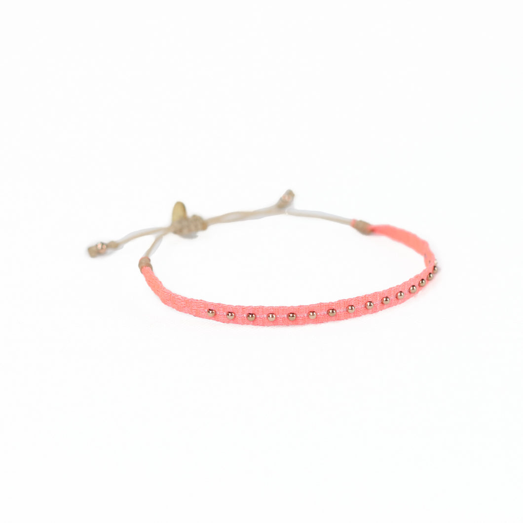 Woven friendship bracelet woven in  bright coral threads with small brass plated beads. Waxed cord adjuster for fit.