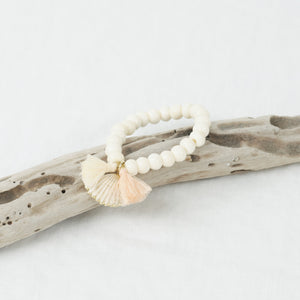 Stretch bracelet made of bone beads with a shell and mini blush tassels.