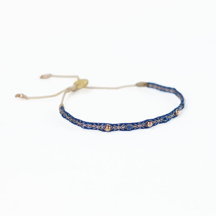 Deep azure blue woven friendship bracelet with brass beads and gold thread. Adjustable waxed cord for fit.