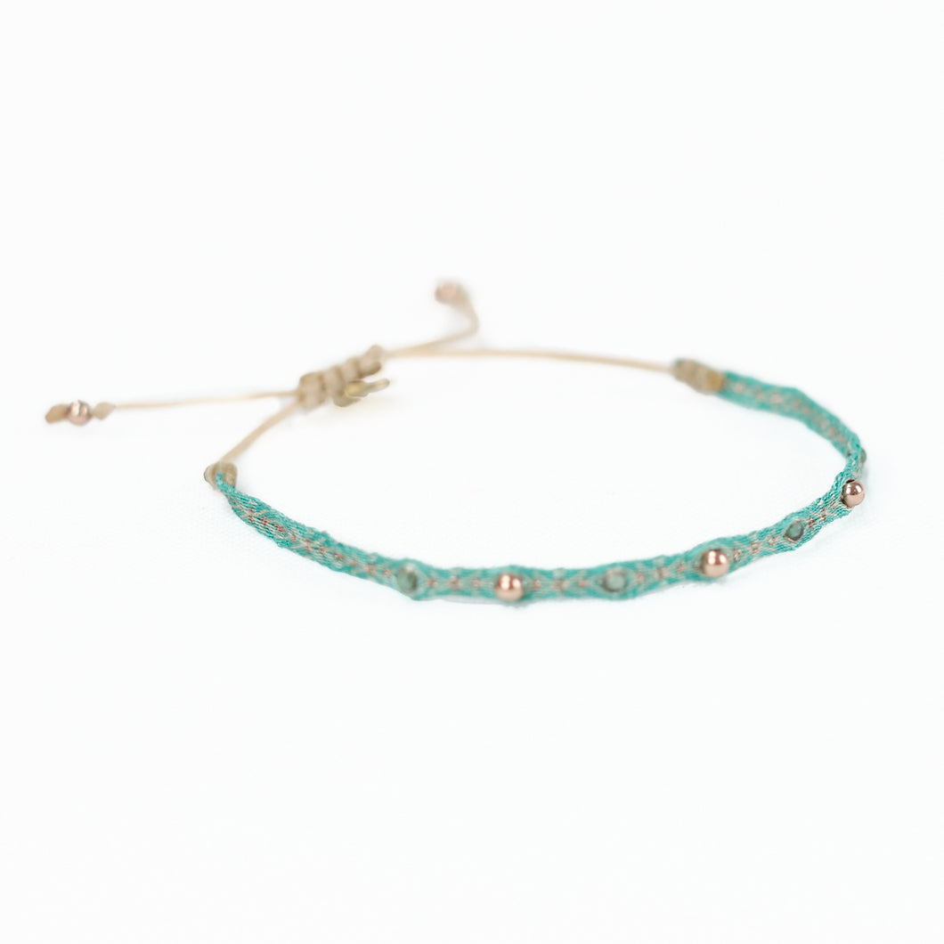 Aqua-Green woven friendship  bracelet embellished with gold thread, jade and brass plated beads. Adjustable waxed cord closure.