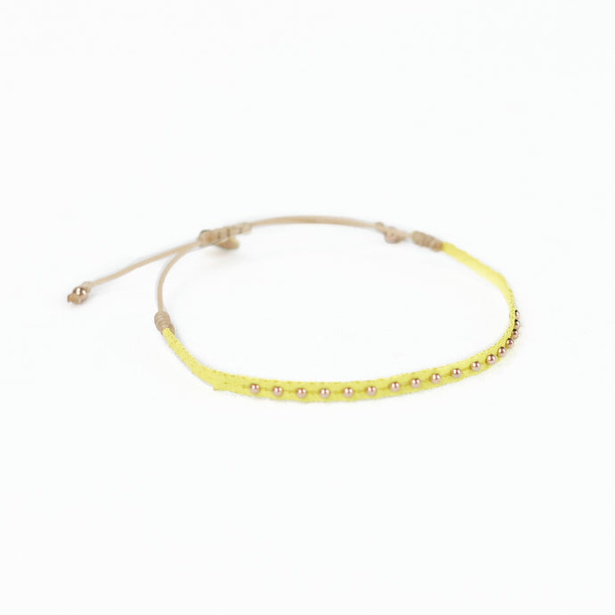 A neon yellow woven friendship bracelet embellished with brass plated beads. Adjustable waxed cord closure.