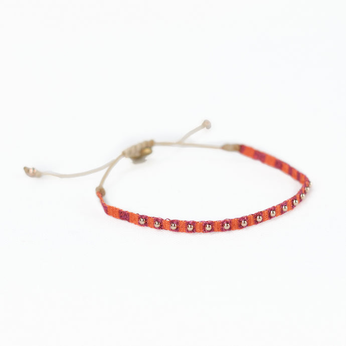Orange and red woven friendship bracelet embellished with gold plated beads. Adjustable wax cord closure.
