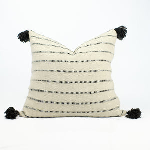 Pillow made of soft natural wool in cream with black stripes and black poms by Treko Wool.