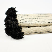 Load image into Gallery viewer, Cream wool blanket with black stripes and black poms by Treko Wool.