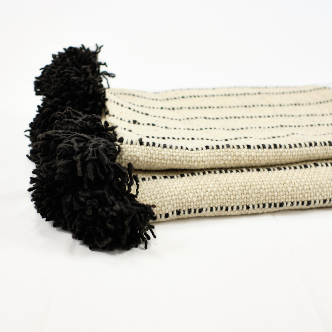 Cream wool blanket with black stripes and black poms by Treko Wool.
