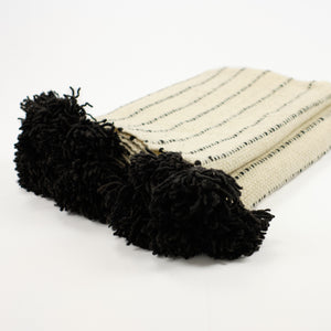 Artisan wool blanket in cream with black stripes and black pom by Treko Wool.