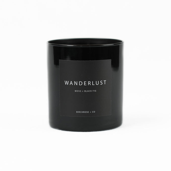 The Wanderlust candle by Birchrose is the scent of Moss and Black Fig. The candle is poured into a black high gloss glass vessel.