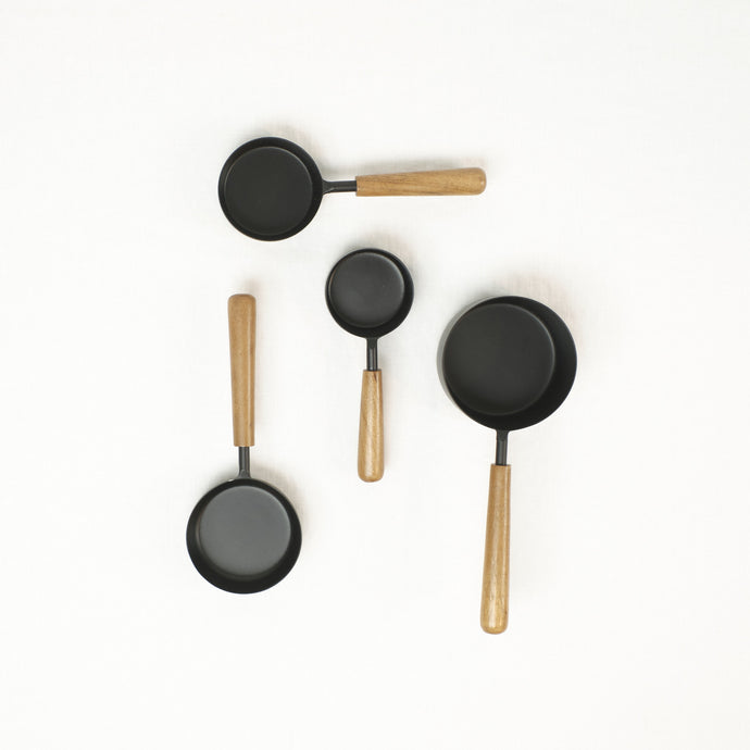 Set of 4 black measuring cups with natural wood handles.