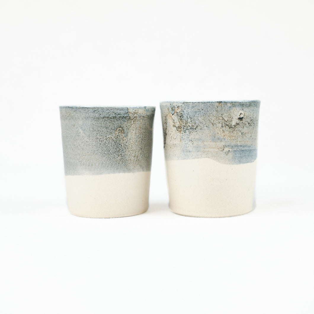 Two small cream color ceramic cups, dipped in a blue-grey glaze by Totem Home.