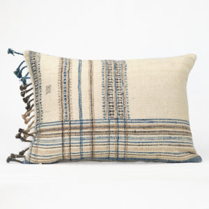 Cream throw pillow with blue, tan and brown plaid pattern and blanket fringe trim