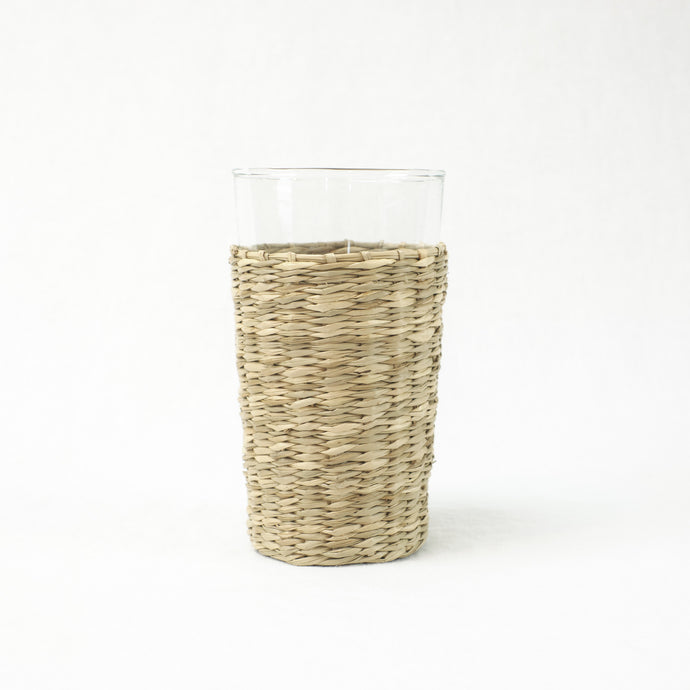 Clear glass highball with dried seagrass cover. Made of recycled glass.