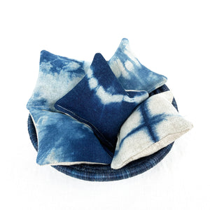 "Basket filled with indigo shibori lavender pillows. Each measures 3"" square."