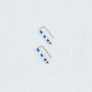 Small beaded earrings in a blue and white stripe pattern with a tiny dark red bead to finish. Blue & white earrings by Alice Rise.