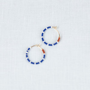 Small beaded hoop earrings made from blue, white & red Japanese glass beads. Made by Alice Rise.