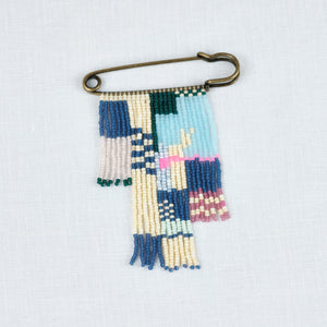 Brass Pin beaded with strings of blue, cream, pink, light blue & red glass beads. A colorful friendship pin by Alice Rise.