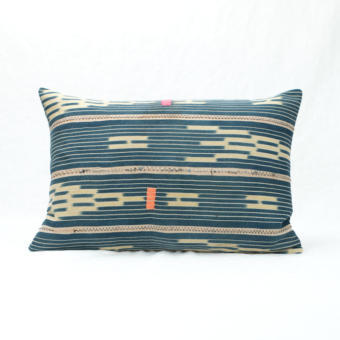 Indigo Baule Pillow with neon pink and orange decorative stitching. Small rectangular shape.
