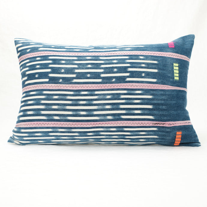 Bright indigo Baule pillow with soft pink stripes and an ivory pattern.