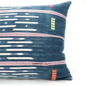 Close up of indigo Baule pillow with hand mending and neon decorative stitching.