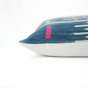 Side view of bohemian pillow with indigo patterned face and white linen back.