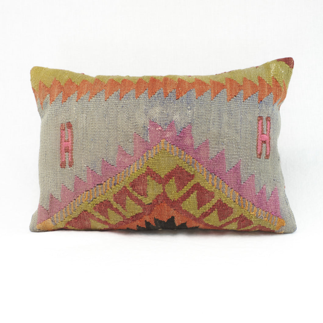 Vintage kilim pillow in shades of red, orange, sunflower, blue & magenta. Faded in color  with a khaki twill back.