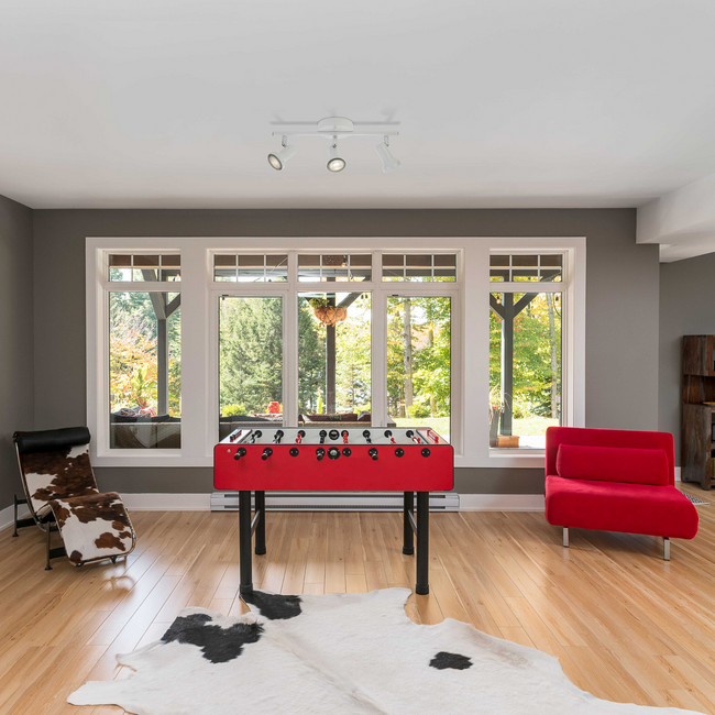 Summerhill Track Lighting Kit hanging on a white ceiling above a modern living space with red and black furniture