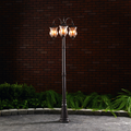 Iilluminated bronze lamp post installed in concrete and surrounded by a garden